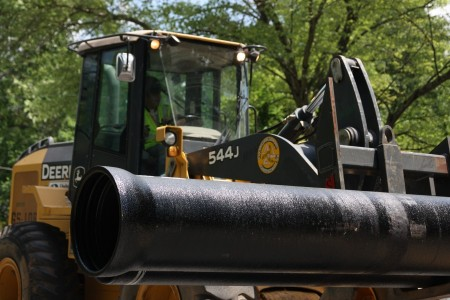 A construction truck moves a section of pipe for the DeKalb County water main replacement project ongoing on Mount Vernon Road in Dunwoody. Photo by Ellen Eldridge