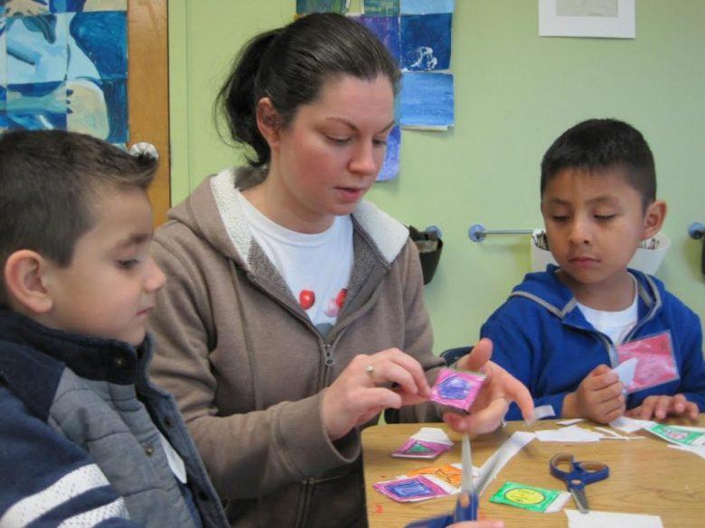 Los Ninos Primero art teacher Alison Calefati helps 4-year-olds (from left) Emiliano Salas, 4, and Edwin Esteva, 5, create an educational game.