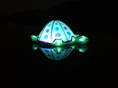 A turtle-shaped lantern floating on the Chattahoochee River in a recent test run for the June 18 Sandy Springs Lantern Parade. (Special)