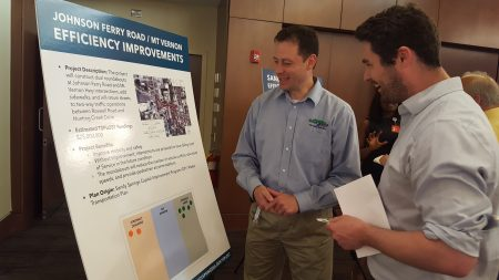 Andrew Thompson (left), the city's capital projects manager, discusses the Mount Vernon Highway/Johnson Ferry Road roundabouts projects with a resident during a May 11 Sandy Springs T-SPLOST project list meeting at Heritage Sandy Springs. (Photo John Ruch)