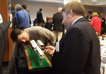 """Audience members (including, at right, Brookhaven Public Works Director Richard Meehan) examine a model of Owens Transit Group's proposal """"HighRoad"""" monorail at the May 13 Perimeter Business Alliance meeting at the Westin Atlanta Perimeter North hotel. (Photo John Ruch)"""