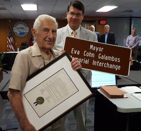 Dr. John Galambos (left) receives a proclamation and miniature sign from Mayor Rusty Paul recognizing the interchange naming at a June 7 City Hall ceremony. At rear, City Council members Tibby DeJulio and Andy Bauman look on, backed by a portrait of Eva Galambos. (Photo John Ruch)