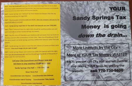 One side of the anonymous postcard calling for Sandy Springs to settle its legal battles with adult businesses. (Photo John Ruch)