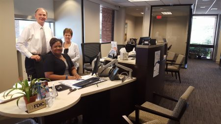From left, Chris Burnett, market president at the Bank of Sandy Springs, Tiffany Kennybrew, assistant banking center manager, and Cindy Miller, banking specialist, at a desk and chair area for customers, instead of the traditional teller line. (Photo John Ruch)