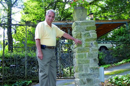 Bruce Cusmano stands at his gate on Evergreen Drive that was damaged in April by a car during a police chase. (Photo John Ruch)