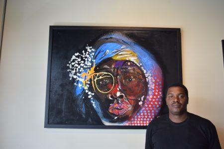 Dakoro with one of his paintings. (Photo Jaclyn Turner)