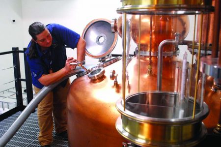 Justin Manglitz, partner and distiller at American Spirit Whiskey Distillery, pumps mash from the fermenter into the wash still on Aug. 20. The whiskey-making business opened for public tours and tastings last month on Armour Drive. (Photo Phil Mosier)