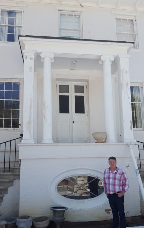 Dr. Robin Fowler at the Thorton House's rear entrance, next to an oval window that has been rehabilitated back to working order. (Photo John Ruch)