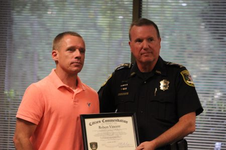 Dunwoody Police Chief Billy Grogan, right, presents a certificate to Robert Vincent and thanking him for saving the life of a tractor-trailer driver. (Photo Dyana Bagby)
