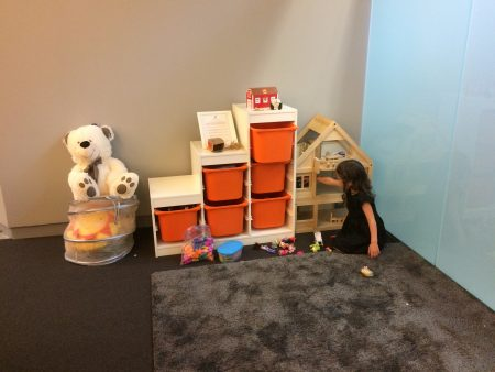 """Mila Sagel, 3, plays with a dollhouse at the new """"Pray Ground"""" at Congregation Or Hadash in Sandy Springs. Children younger than five can play in this area while they listen to services. (Photo Tali Medwed)"""