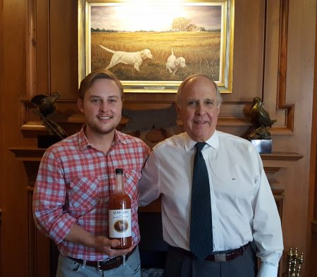 Nat (left) and Pete Hendricks pose with a bottle of Sister's Sauce under a painting depicting the mix's namesake, Sister the bird dog, at their Sandy Springs office. (Photo John Ruch)