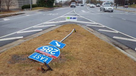 A highway sign was apparently damaged by a vehicle driving onto a pedestrian island in the Ashford-Dunwoody diverging diamond. (Photo John Ruch)