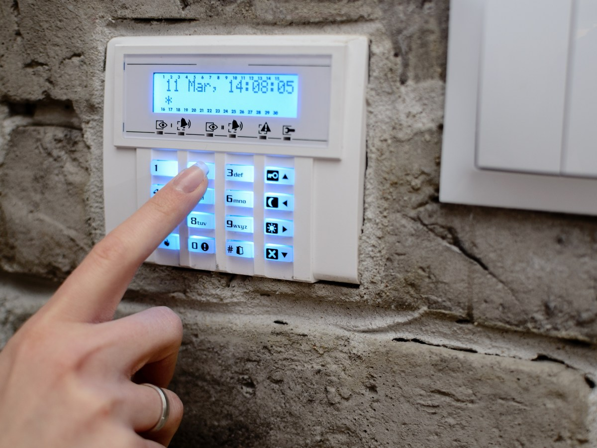 a hand pushing security alarm buttons