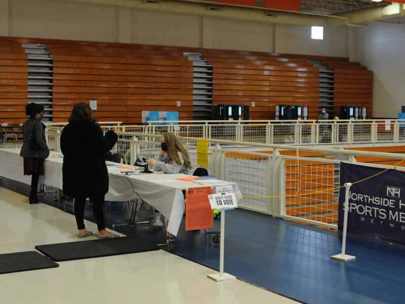 Poll workers assist voters at the gym at North Springs High School in Sandy Springs.