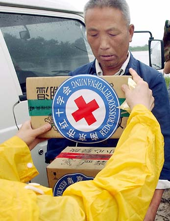 A Chinese farmer receives food aid from the Red Cross after his home was flooded, in Chuhe, which lies between China's Anhui and Jiangsu province 11 July 2003. The worst flooding China has seen in years has so far killed 569 people and forced the emergency evacuation of 2.29 million, with more than 505,000 homes had collapsed and another 1.33 million homes been damaged by floods that have mainly occurred in central, east and southern China since late May, with economic losses nationwide risen to 39.87 billion yuan (4.8 billion dollars). AFP PHOTO