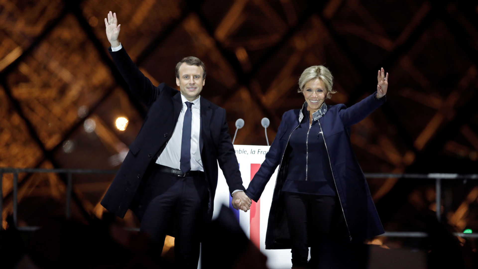 French President elect Emmanuel Macron and his wife Brigitte Trogneux celebrate on the stage at his victory rally near the Louvre in Paris, France May 7, 2017. REUTERS/Benoit Tessier - RTS15KRV