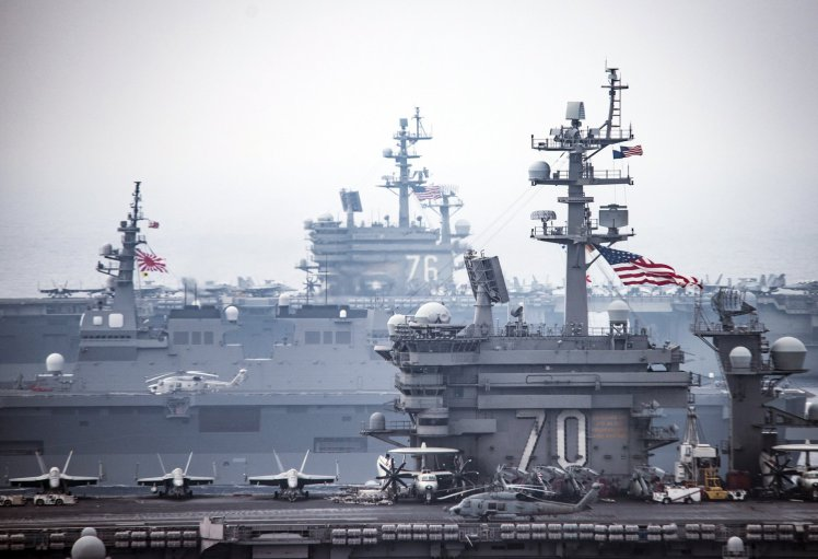 In this image released by the U.S. Navy, aircraft sit on the flight deck of the aircraft carrier USS Carl Vinson (CVN70), Thursday, June 1, 2017, in the western Pacific region. The Japan Maritime Self-Defense Force and U.S. Navy forces routinely train together to improve interoperability and readiness to provide stability and security for the Indo-Asia Pacific region. The USS Ronald Reagan (CVN 76), rear, and Japan's Hyuga, left, are in the background. (Spc. 2nd Class Z.A. Landers/U.S. Navy via AP)