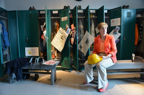Dr. Donna DeBlasio sits in a locker room display. She is a professor of history at Youngstown State University and serves as advisor and volunteer at the museum.