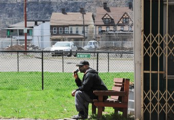 A man talks on his cellphone in the space along the main street where a store once stood