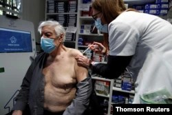 FILE - A pharmacist administers the AstraZeneca COVID-19 vaccine to a patient in a pharmacy in Paris as part of the coronavirus disease vaccination campaign, March 19, 2021.