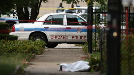 CHICAGO, IL - SEPTEMBER 20:  Police investigate the shooting death of 14-year-old Tommy McNeal, whose body is covered by a sheet on the sidewalk on September 20, 2013 in Chicago, Illinois. McNeal was one of at least 3 killed and about 30 wounded by gunfire in the city in the past 24 hours.  (Photo by Scott Olson/Getty Images)