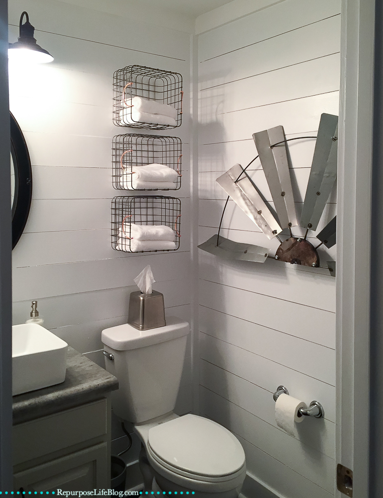 modern farmhouse style guest bathroom with shiplap walls, 3 baskets on the wall with white towels, and tissue dispenser on back of toilet