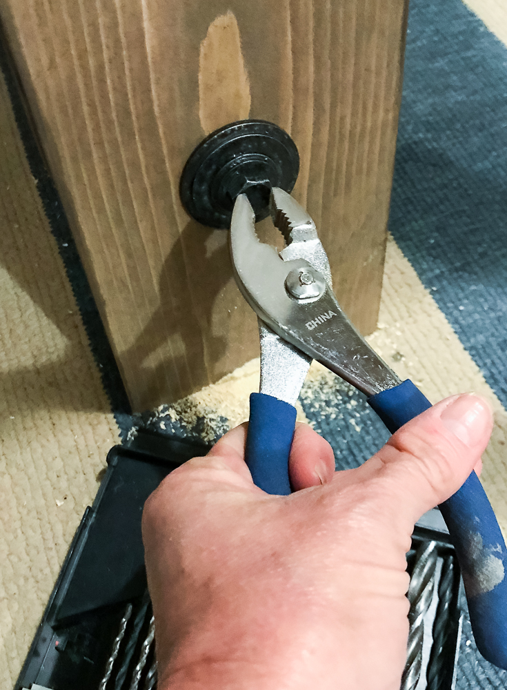 pliers being used to tighten bolt
