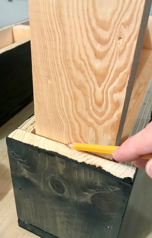 2x4 in wooden box marked with pencil