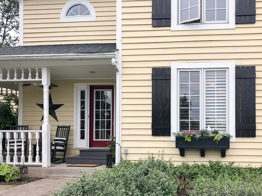 yellow house with flower box and shutters