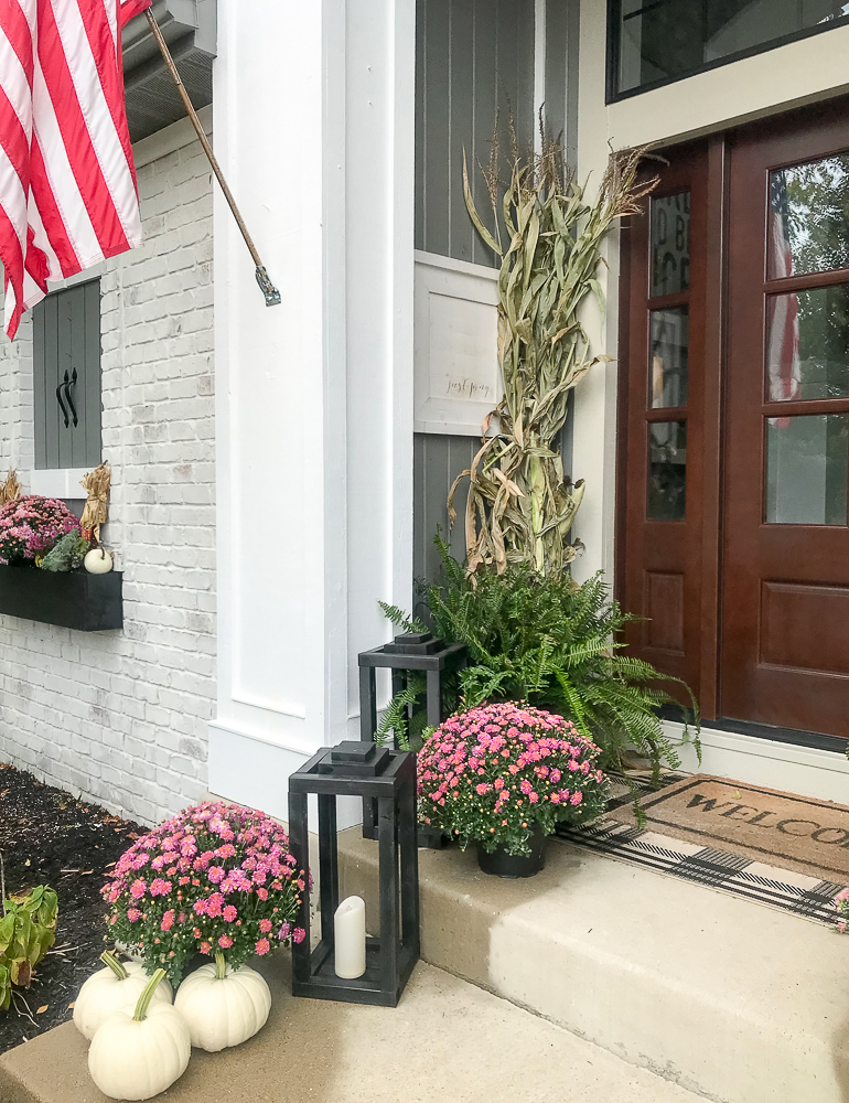 front porch with mums, fern, and lanterns