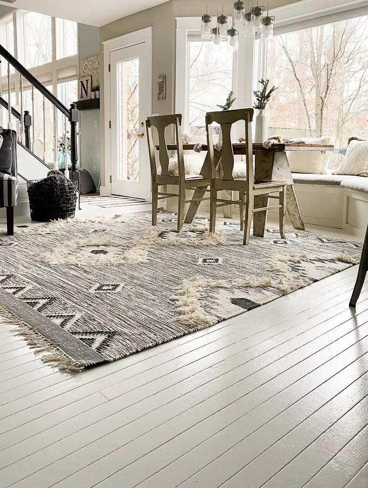 Kitchen table on a boho style rug on white painted hardwood floors
