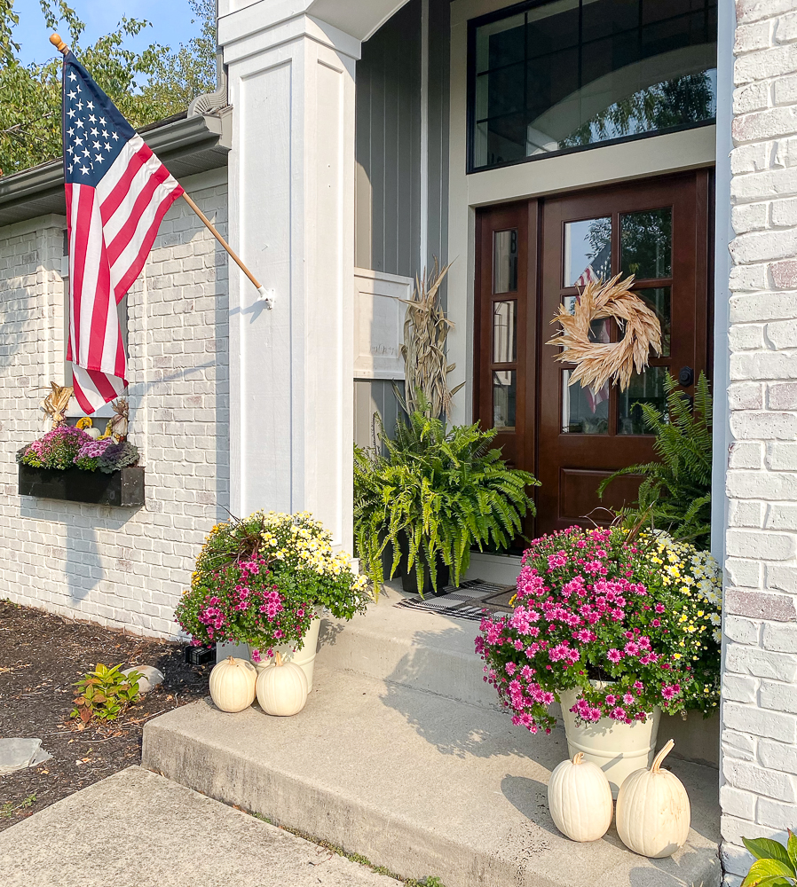 front porch with mums, ferns, white pumpkins and American Flag