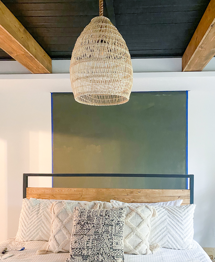Green accent wall behind a bed and pendant light