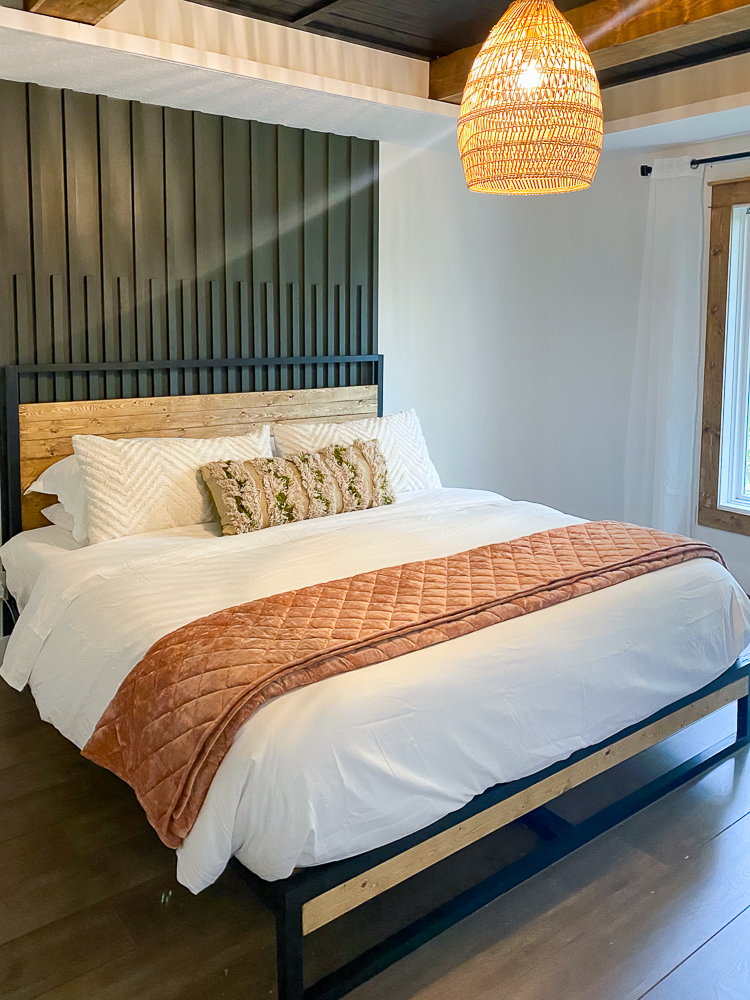 King size bed with a blush pink quilt folded across it in the master suite