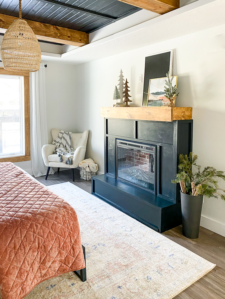 Master bedroom with fireplace and comfy chair