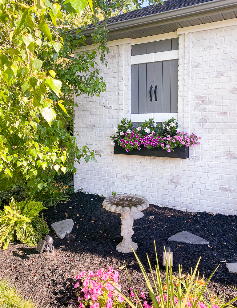Flower box with pink and white flowers on a white brick house