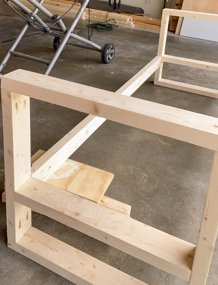 2x4 propped up using boards to jig into two armrests