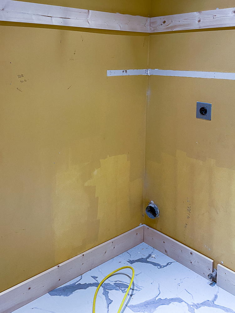 Yellow walls in a laundry room with bare baseboards