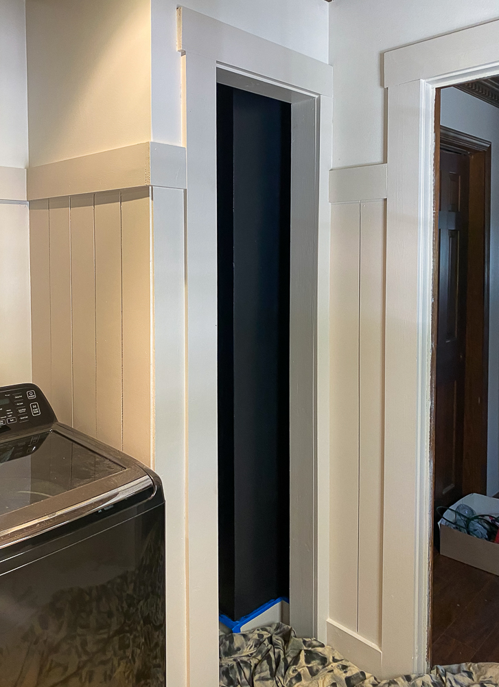Putty color vertical shiplap with washing machine in a laundry room