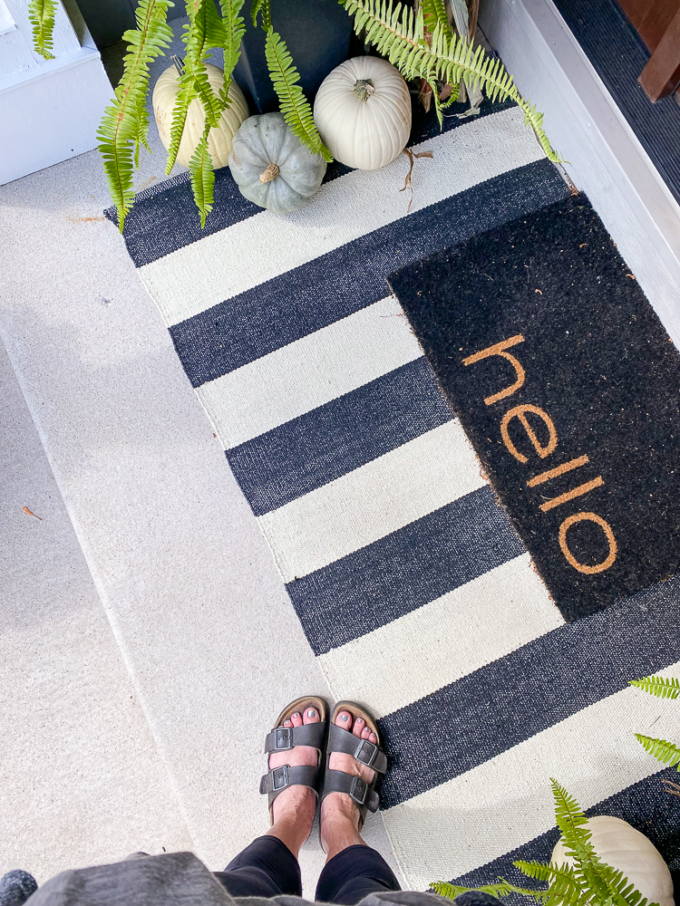Ladies feet in an outdoor fall decorating front porch scene with pumpkins, striped rug, hello rug and ferns