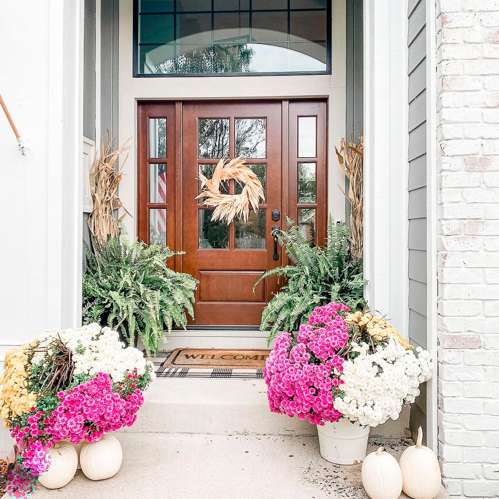 Front porch with outdoor fall decorating: mums, pumpkins, wreath, corn shocks