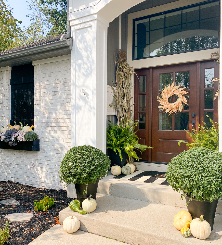 Front view of a house with outdoor fall decorating throughout the porch and front of home