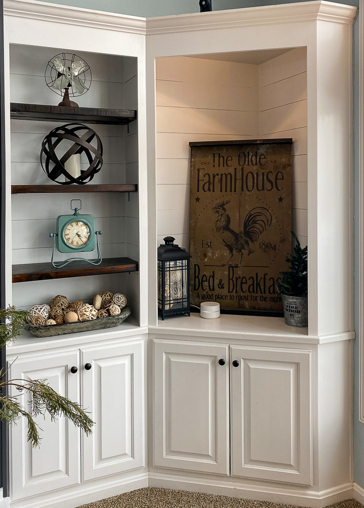 A corner cabinet painted white with shiplap inside and a lot of decor
