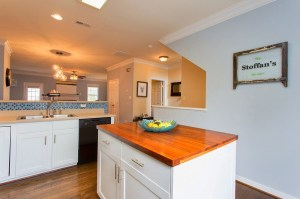Efficient Kitchen with Large Butcher Block Island Provides Extra Storage and Food Prep Space