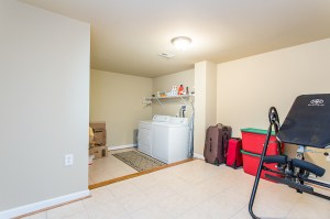 Separate Tiled Laundry Room with Storage Closet and Work Space