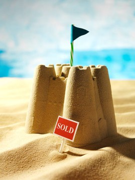 """sandcastle on sunny day with """"sold"""" sign out front"""
