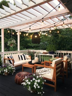 beautiful backyard patio with hanging plants and fairy lights above seating