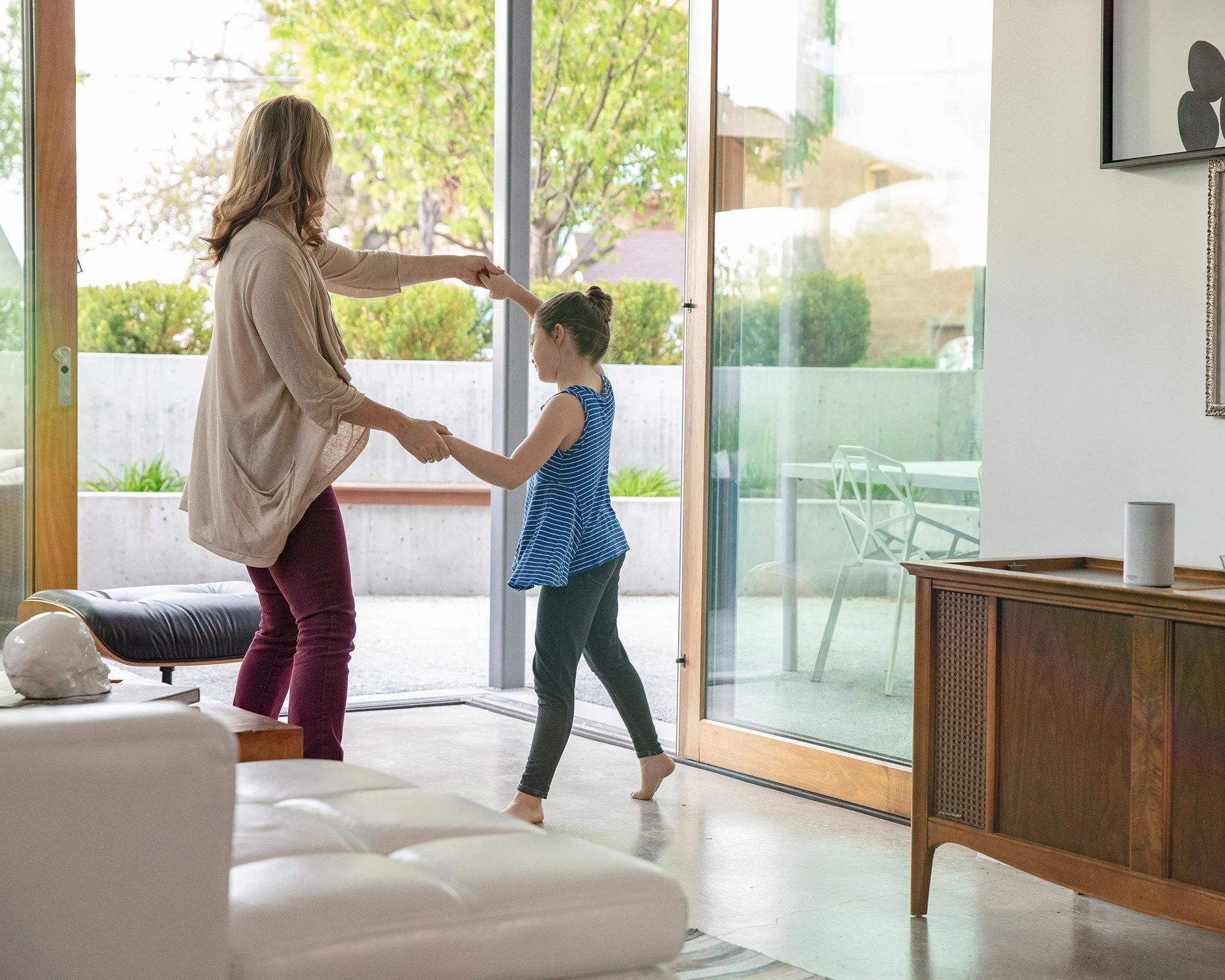 hight resolution of mother and daughter dancing to connected whole home distributed audio speakers
