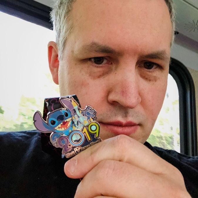 "Photo of David Demaree holding up a Disney World ""2019"" pin featuring Stitch"