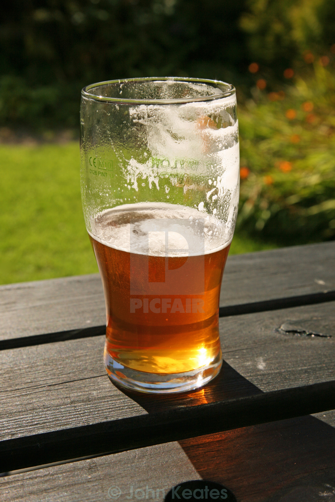A Pint Glass Of Real Ale Beer Either Half Full Or Half